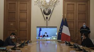 French President Emmanuel Macron is seen on a screen from his presidential residence in Versailles as he attends by video conference the weekly cabinet meeting at the Elysee Palace (Julien de Rosa/AP)