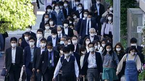 People wear masks as they commute during the morning rush hour Thursday, May 7, 2020, in Tokyo. Prime Minister Shinzo Abe announced that Japan extend a state of emergency until end of May. (AP Photo/Eugene Hoshiko)