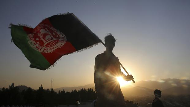 FILE – In this Aug. 19, 2019, file photo, a man waves an Afghan flag during Independence Day celebrations in Kabul, Afghanistan. An Afghan official Sunday, Feb. 9, 2020, said multiple U.S. military deaths have been reported in Afghanistan's Nangarhar province after an insider attack by a man wearing an Afghan army uniform. (AP Photo/Rafiq Maqbool, File)