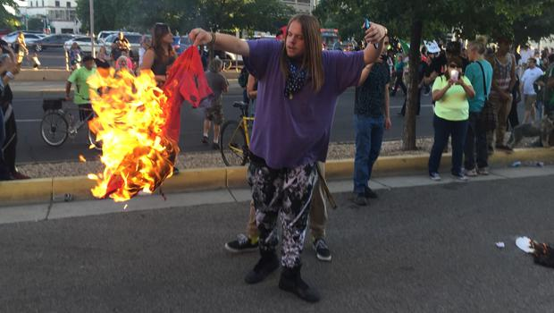 An protester against Donald Trump holds a burning T-shirt outside the Republican's rally in Albuquerque (AP)