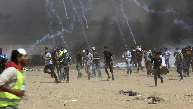 Palestinian protesters run for cover