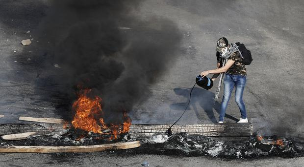 An anti-government protester drops oil on burning tyres and wood in Beirut (AP)