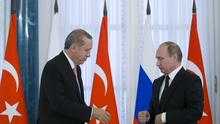 Russian President Vladimir Putin and Turkish President Recep Tayyip Erdogan shake hands during a news conference (AP)