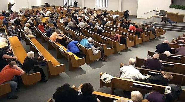 Churchgoers take cover while a congregant armed with a handgun, top left, engages a man who opened fire, near top centre just right of windows (West Freeway Church of Christ/Courtesy of Law Enforcement via AP)