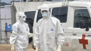 Health workers wearing protective gear wait to carry out the body of a person suspected to have died from Ebola in Monrovia, Liberia (AP)