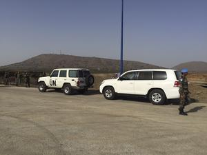 UN vehicles, soldiers and officials gather at the Quneitra border crossing (AP)
