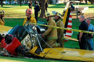 Firefighters inspect the cockpit of Harrison's Ford plane on an LA golf course yesterday