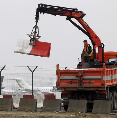 Workers place concrete blocks to stop access to a security fence at Brussels international airport (AP)