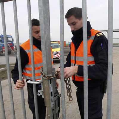 Two airport police officers use a chain to lock a gate at Brussels international airport (AP)