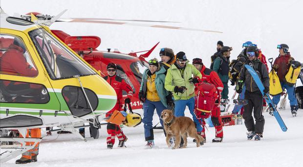Rescue workers and helicopters involved in the search following an avalanche in Andermatt, Switzerland (Urs Flueeler/Keystone via AP)