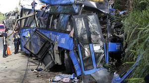 Police investigators beside the wreckage of the bus (AP)