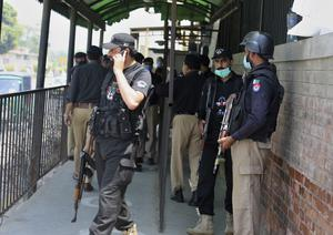 Police officers gather at an entry gate of the district court (AP/Muhammad Sajjad)