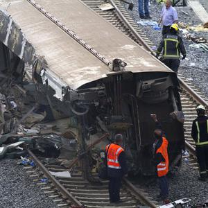 Rail personnel and firefighters inspect derailed cars at the site of a train accident in Spain (AP)