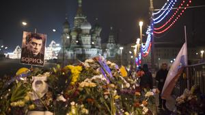People walk to pay their respects at the place where Boris Nemtsov was gunned down on Friday (AP)