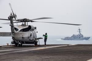 An MH-60R Sea Hawk on the flight deck of the USS Ronald Reagan as USS Mustin steams alongside in the South China Sea (Mass Communication Specialist 3rd Class Erica Bechard/US Navy/AP)