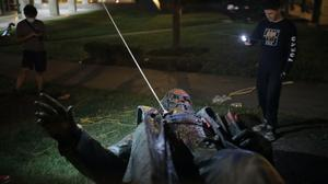 People film the only statue of a Confederate genera, in the nation's capital after it was toppled by protesters and set on fire (Maya Alleruzzo/AP)
