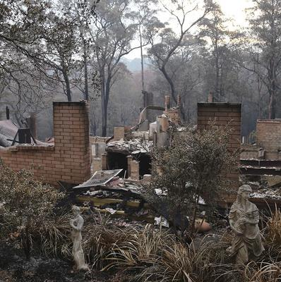 A house sits in ruins in Sunny Ridge Drive in Winmalee, 40 miles from Sydney after a wildfire swept through the street burning several homes (AP)