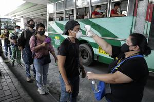 People have their temperatures checked before boarding a bus during the first day of a more relaxed lockdown in Manila, Philippines (Aaron Favila/AP)