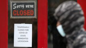 A pedestrian walks past The Framing Gallery, closed due to the Covid-19 pandemic, in Grosse Pointe, Michigan (Paul Sancya/AP)