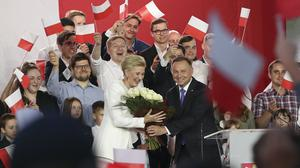 Andrzej Duda, right, and his wife Agata Kornhauser-Duda smile while greeting supporters at the end of the election day in Pultusk, Poland (Czarek Sokolowski/AP)
