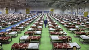 A member of the Iranian army walks past rows of beds at a temporary 2,000-bed hospital (AP)