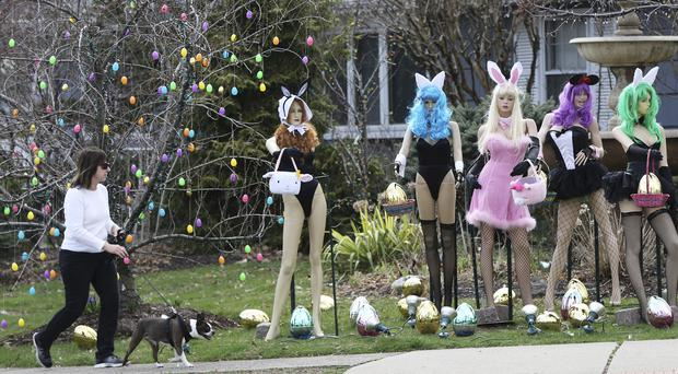 A woman walks her dog past a racy Easter display in New Jersey (Kevin R Wexler/The Record via AP)