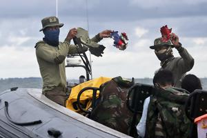 Indonesian navy divers show parts of aircraft recovered from the Java Sea (Tatan Syuflana/AP)