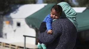 A migrant woman carries her baby at the Kara Tepe camp for refugees and other migrants on the Greek island of Lesbos (AP)