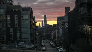 A man crosses a street against the backdrop of One World Trade Centre at dusk in New York (Wong Maye-E/AP)