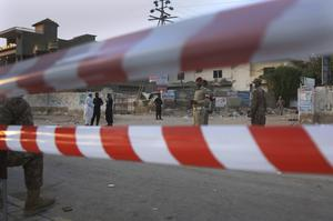 Pakistan army soldiers and police commandos stand guard while they cordon off a street leading to the site of the plane crash in Karachi (Fareed Khan/AP)