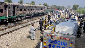 Soldiers and officials examine a train damaged by a fire in Liaquatpur, Pakistan (Siddique Baluch/AP)