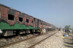 Pakistani officials examine the train (Siddique Baluch/AP)