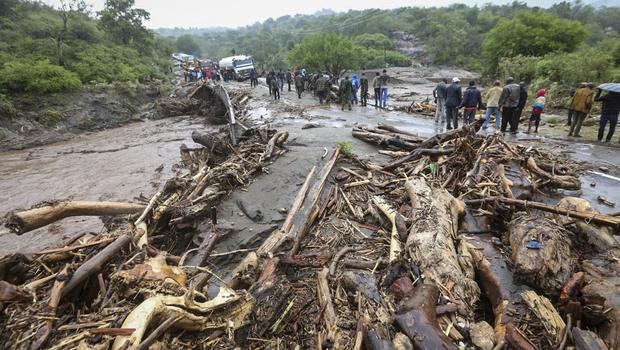 Passengers from stranded vehicles stand next to the debris from floodwaters in Kapenguria, Kenya (AP Photo)