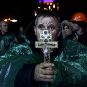 An anti-government protester holds a crucifix as he prays at Independence Square in Kiev, Ukraine (AP)