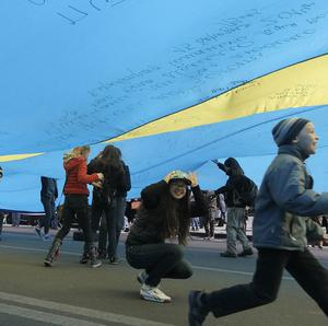 Ukrainian children play under a huge yellow-and-blue Ukrainian national flag at a rally in Kiev's main square (AP)