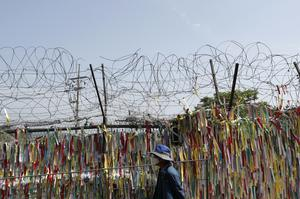 A visitor wearing a face mask walks in front of the wire fence decorated with ribbons written with messages wishing for the reunification of the two Koreas (Lee Jin-man/AP)
