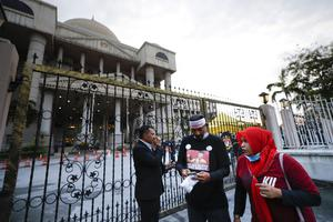 Supporters of Najib wait outside court (Vincent Thian/AP)