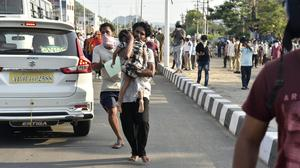 A man runs carrying a child affected by a chemical gas leak in Vishakhapatnam, India (AP)