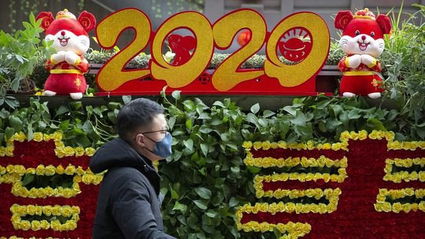 A traveler wearing a face mask walks past a display for the upcoming Lunar New Year, the Year of the Rat, at the Beijing West Railway Station (AP)