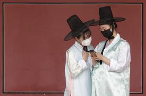 Women wearing face masks to help protect against the spread of the new coronavirus watch a mobile phone at the Gyeongbok Palace in Seoul (AP)