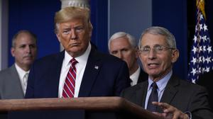 President Donald Trump listens as Director of the National Institute of Allergy and Infectious Diseases Dr. Anthony Fauci speaks during a coronavirus briefing at the White House on Friday (Evan Vucci/AP)