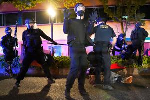 A protester holds his hands in the air while walking past an arrest in Portland