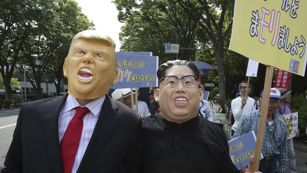Protesters wearing masks of US President Donald Trump and North Korean leader Kim Jong Un march with others at a May Day rally in Tokyo (Koji Sasahara/AP)