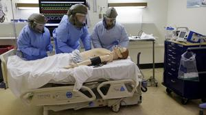 Medical workers wearing protective equipment at a media demonstration on dealing with possible Ebola patients. (AP)