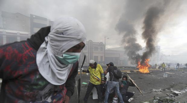 Anti-government demonstrators clash with the police near the national assembly building in Quito (Dolores Ochoa/AP)