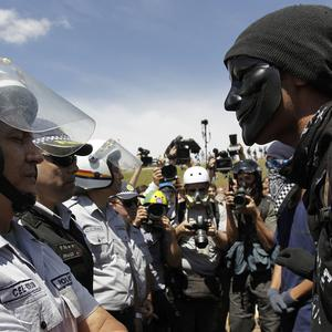 A masked demonstrator confronts police during protests after the military ceremony of Independence Day in Brasilia, Brazil (AP)