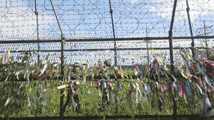 South Korean army soldiers wearing face masks pass by a wire fence decorated with ribbons urging reunification of the two Koreas at the Imjingak Pavilion in Paju, near the border with North Korea (Ahn Young-joon/AP)