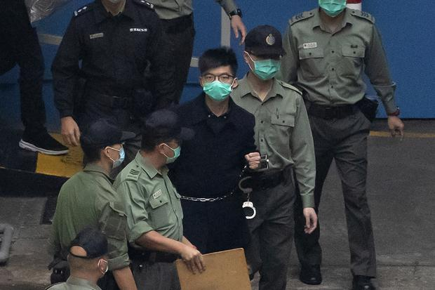 Activist Joshua Wong, centre, is escorted by officers to a prison van (Kin Cheung/AP)