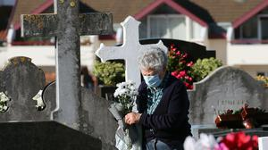 A woman holds flowers as she walks between graves at Saint Jean de Luz cemetery, southwestern France