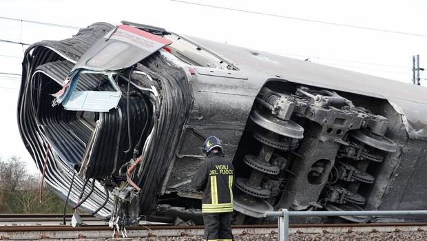 A firefighter inspects a derailed train carriage, near Lodi, northern Italy (Antonio Calanni/AP)